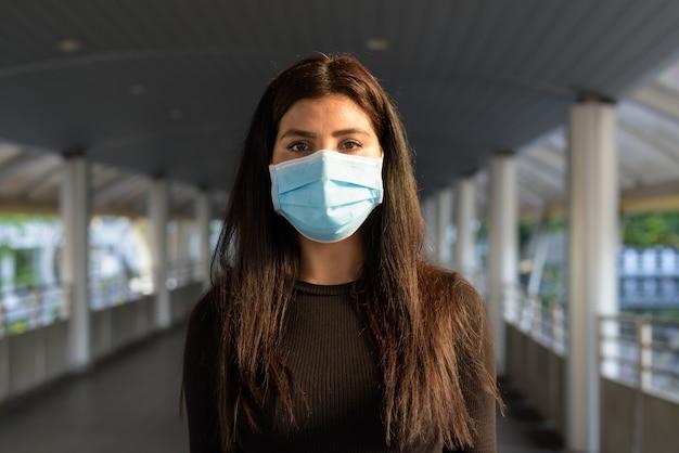 Młoda hinduska w masce dla ochrony przed epidemią koronawirusa na kładce