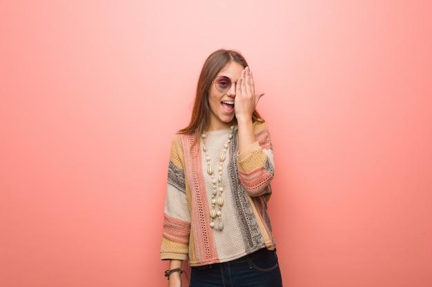 Młoda hipis kobieta na różowej rozkrzyczanej szczęśliwej i nakrycia twarzy z ręką