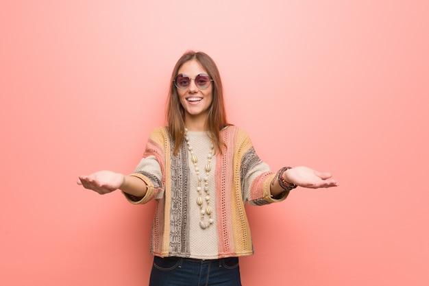 Młoda hipis kobieta na różowej ścianie zaprasza przyjechać