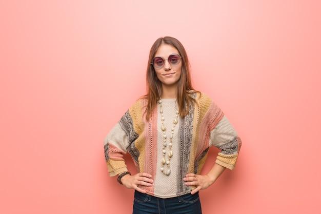 Młoda hipis kobieta na różowo z rękami na biodrach