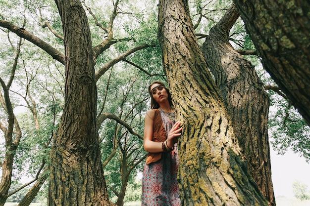 Młoda hipis kobieta na spacerze po lesie