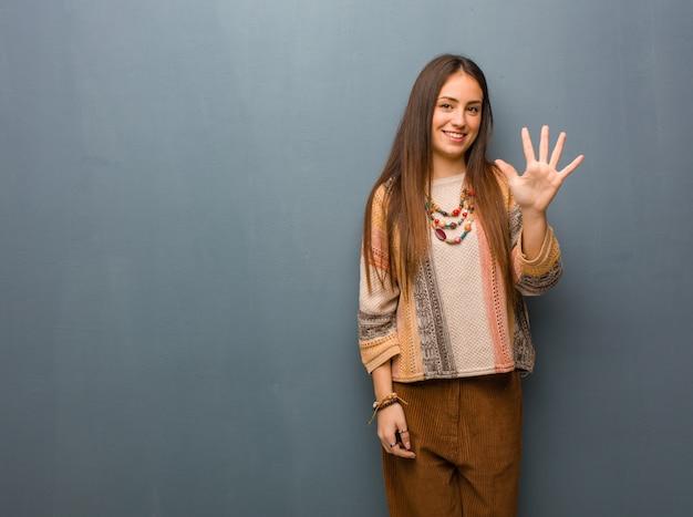 Młoda hipis kobieta pokazuje liczbę pięć