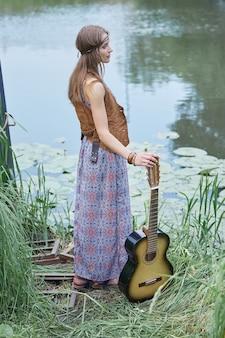Młoda hipis kobieta stojąca w pobliżu leśnego jeziora