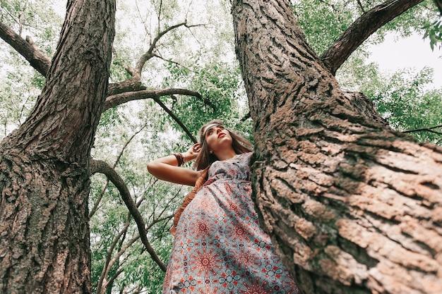 Młoda hipis kobieta stojąca w pobliżu starego drzewa