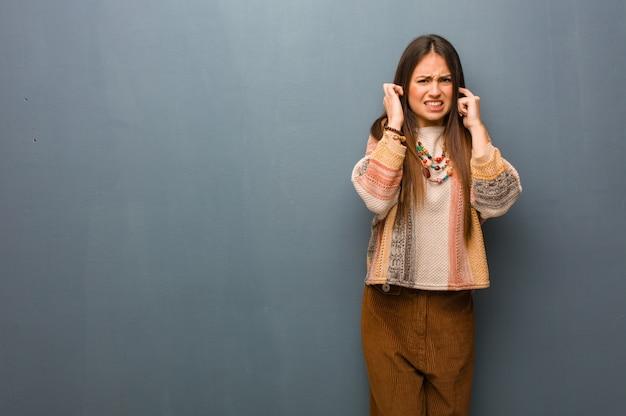 Młoda hipis kobieta zakrywa ucho z rękami