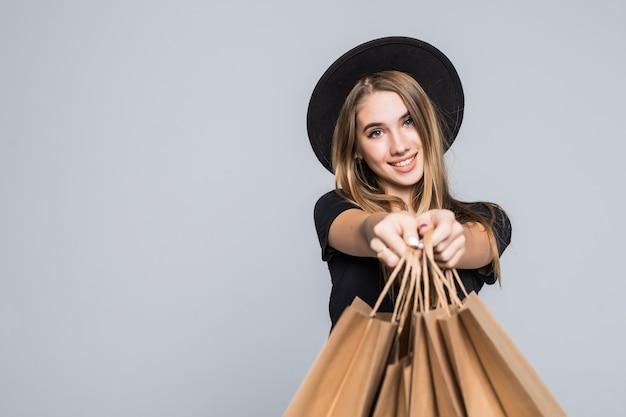 Młoda hipster dziewczyna ubrana w czarny t-shirt i skórzane spodnie trzymając puste torby na zakupy z uchwytami na białym tle