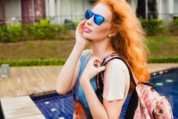 Młoda hipster imbirowa szczupła kobieta idzie na siłownię, czerwone włosy kolorowe, niebieskie okulary przeciwsłoneczne, styl sportowy, piegi, znamiona, plecak, szczęśliwy, zabawny, fajny strój, uśmiechnięty, zmysłowy, atletyczny, odzież fitness