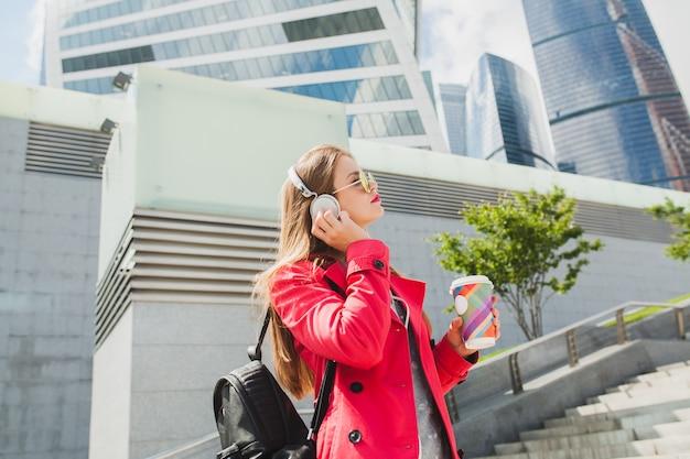 Młoda hipster kobieta w różowym płaszczu, dżinsy na ulicy z plecakiem i kawą, słuchanie muzyki na słuchawkach, na sobie okulary przeciwsłoneczne
