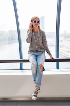 Młoda hipster kobieta w stroju casual, zabawę słuchając muzyki w słuchawkach, nosząc dżinsy, sweter i okulary przeciwsłoneczne, styl miejski siedzi przy oknie z widokiem na miasto
