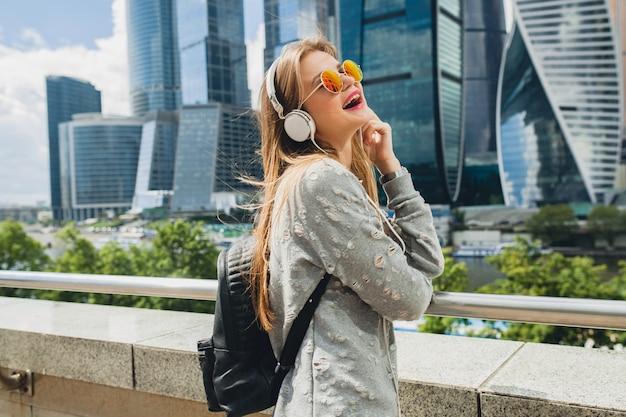 Młoda hipster kobieta, zabawy na ulicy, słuchanie muzyki na słuchawkach, na sobie różowe okulary, miejski styl wiosna lato