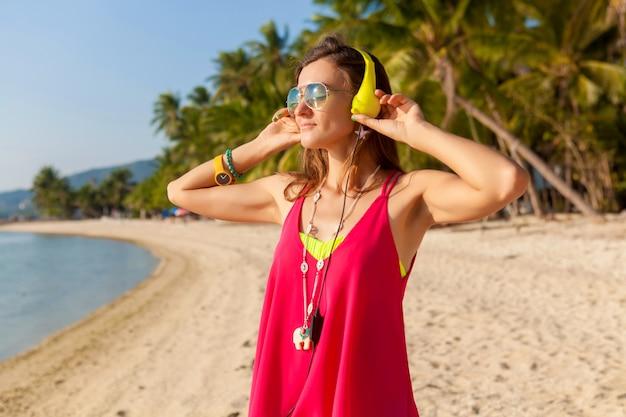 Młoda hipster piękna kobieta, tropikalna plaża, wakacje, kolorowe, letni styl trendu, okulary przeciwsłoneczne, słuchawki, słuchanie muzyki, palmy w tle, uśmiechnięty szczęśliwy, zabawa, szczegóły, portret z bliska