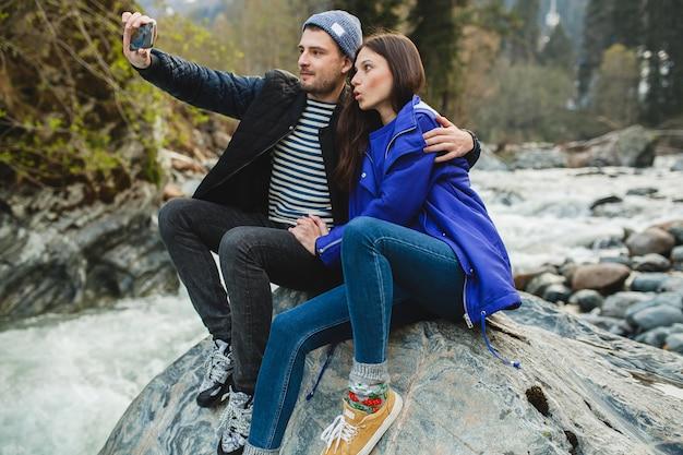 Młoda hipster piękna para zakochanych, trzymając smartfon, robienie zdjęć, siedząc na skale nad rzeką w zimowym lesie