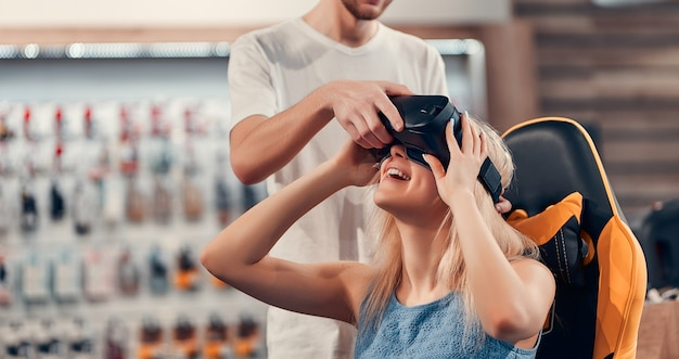 Młoda hipsterka figlarnie zdumiona para bawi się z goglami vr, podczas gdy dziewczyna siedzi na krześle w sklepie technicznym.
