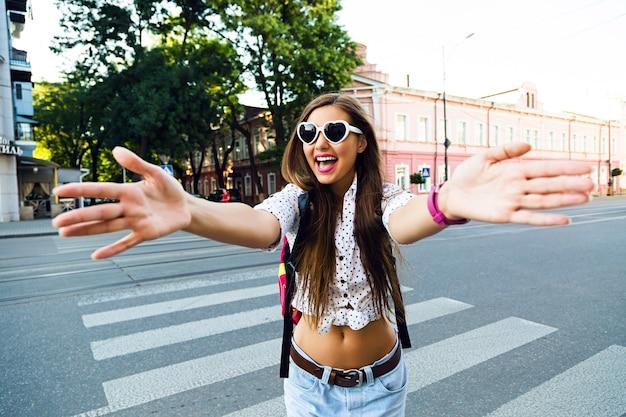 Młoda hipsterka szaleje i bawi się w centrum europy, samotnie spacerując i podróżując, radość, emocje, swobodne stylowe ciuchy i plecak,