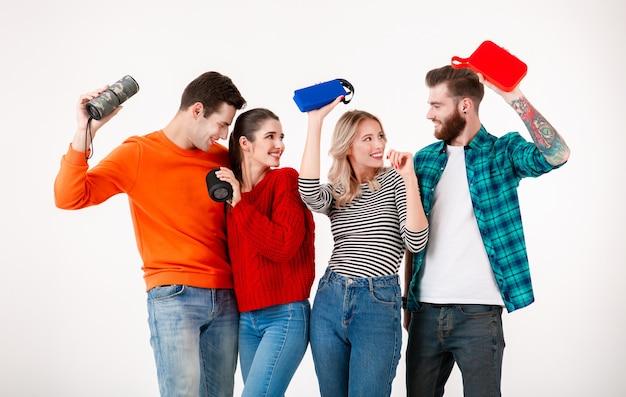 Młoda hipsterska firma przyjaciół bawi się razem uśmiechając się słuchając muzyki na głośnikach bezprzewodowych, tańcząc ze śmiechu