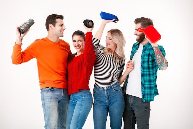 Młoda hipsterska firma przyjaciół bawi się razem uśmiechając się słuchając muzyki na głośnikach bezprzewodowych