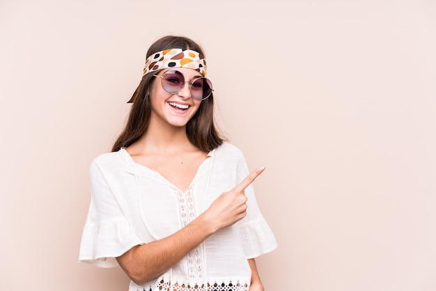 Młoda hipter kaukaski kobieta na białym tle, uśmiechając się i wskazując na bok, pokazując coś w pustej przestrzeni.