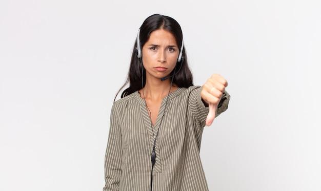 Młoda hiszpanin kobieta czuje krzyż, pokazując kciuk w dół za pomocą zestawu słuchawkowego. koncepcja telemarketingu