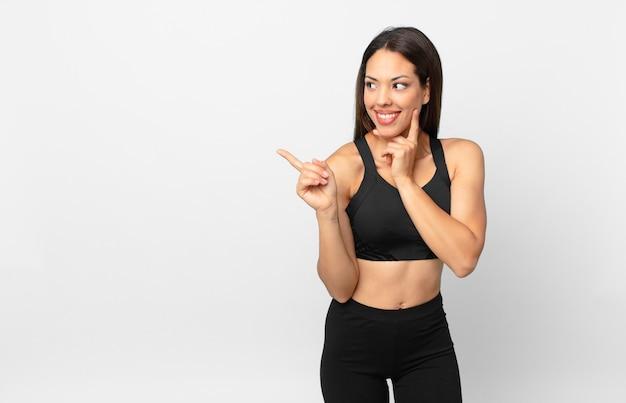 Młoda hiszpanin kobieta uśmiecha się szczęśliwie i marzy lub wątpi. koncepcja fitness