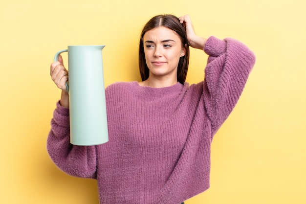 Młoda hiszpanin kobieta uśmiecha się szczęśliwie i marzy lub wątpi. koncepcja termosu do kawy