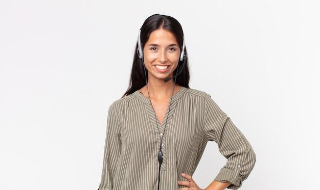 Młoda hiszpanin kobieta uśmiecha się szczęśliwie z ręką na biodrze i pewnie z zestawem słuchawkowym. koncepcja telemarketingu