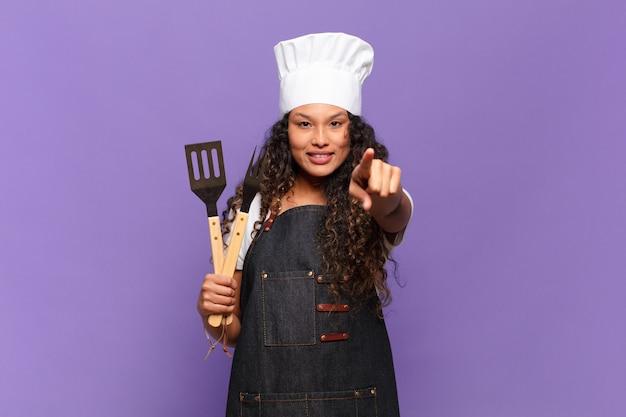 Młoda hiszpanin kobieta, wskazując na aparat z zadowolonym, pewnym siebie, przyjaznym uśmiechem, wybierając ciebie. koncepcja szefa kuchni z grilla
