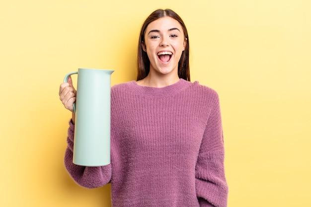 Młoda hiszpanin kobieta wygląda na szczęśliwą i mile zaskoczoną. koncepcja termosu do kawy