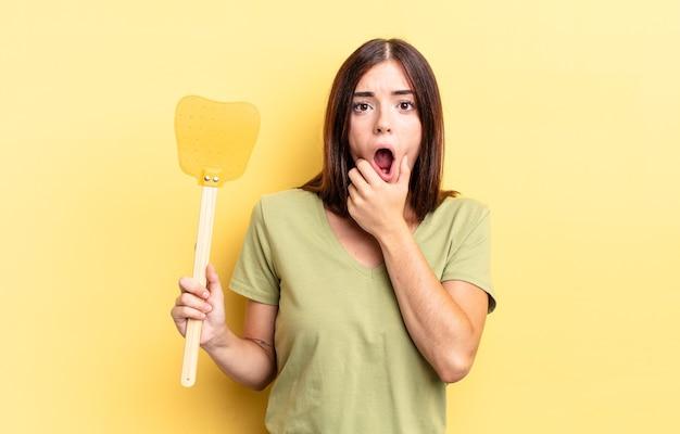 Młoda hiszpanin kobieta z szeroko otwartymi ustami i oczami i ręką na brodzie. koncepcja zabijania much