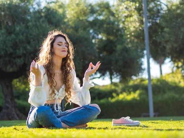 Młoda hiszpanka medytuje siedząc na trawie w wiosennym słonecznym parku