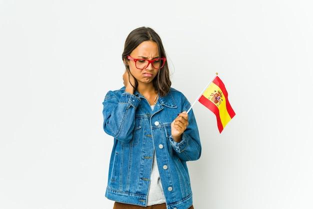 Młoda hiszpanka trzyma flagę na białej ścianie cierpi na ból szyi z powodu siedzącego trybu życia.
