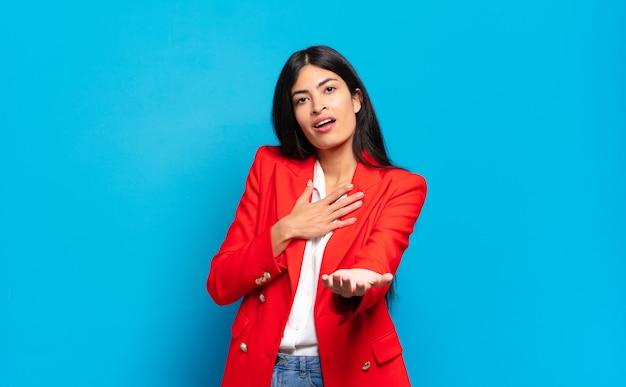 Młoda hiszpańska bizneswoman czuje się szczęśliwa i zakochana, uśmiechając się z jedną ręką obok serca, a drugą wyciągniętą do przodu