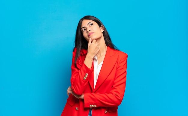 Młoda hiszpańska bizneswoman czuje się zamyślona, zastanawia się lub wyobraża sobie pomysły, marzy i patrzy w górę, aby skopiować przestrzeń