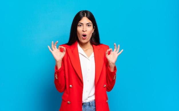 Młoda hiszpańska bizneswoman czuje się zszokowana, zdumiona i zaskoczona, okazując aprobatę, robiąc dobry znak obiema rękami