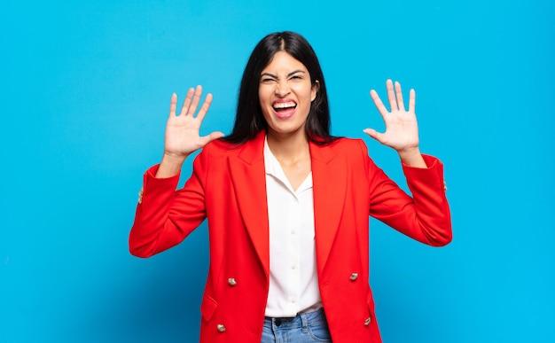 Młoda hiszpańska bizneswoman krzycząca w panice lub złości, zszokowana, przerażona lub wściekła, z rękami przy głowie