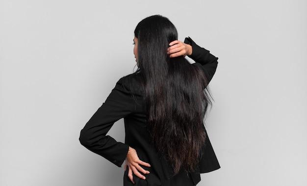 Młoda hiszpańska bizneswoman myśli lub wątpi, drapie się po głowie, czuje się zdezorientowana i zdezorientowana, widok z tyłu lub z tyłu