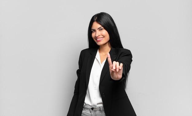 Młoda hiszpańska bizneswoman uśmiecha się dumnie i pewnie, triumfalnie tworząc pozę numer jeden, czując się jak lider