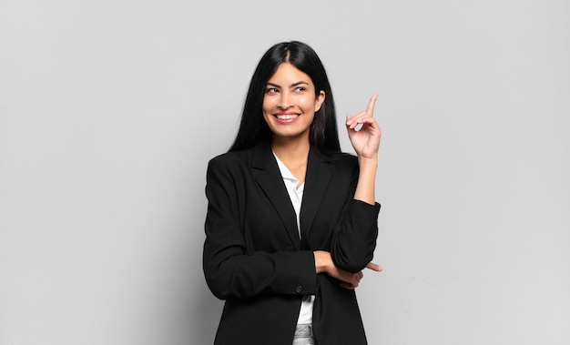 Młoda hiszpańska bizneswoman uśmiecha się radośnie i patrzy w bok, zastanawiając się, myśląc lub mając pomysł