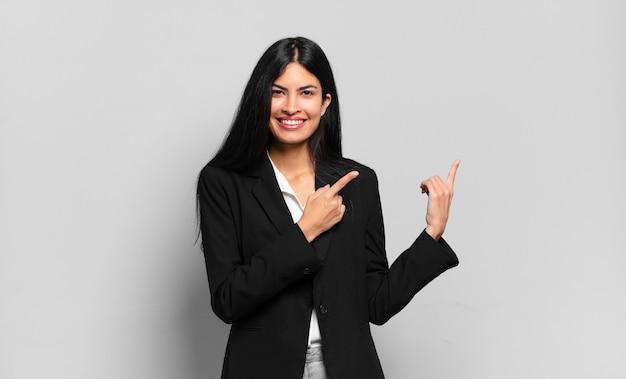 Młoda hiszpańska bizneswoman uśmiecha się radośnie i wskazuje na bok i do góry obiema rękami pokazując obiekt w przestrzeni kopii