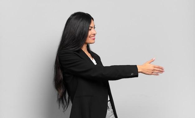 Młoda hiszpańska bizneswoman uśmiecha się, wita cię i oferuje uścisk dłoni, aby zamknąć udaną transakcję, koncepcja współpracy