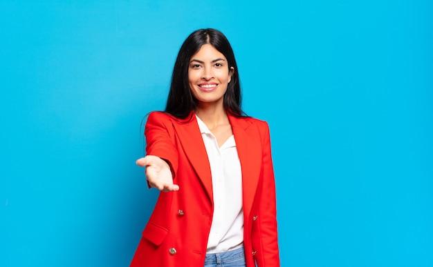 Młoda hiszpańska bizneswoman uśmiechnięta, wyglądająca na szczęśliwą, pewną siebie i przyjazną, oferująca uścisk dłoni, aby zamknąć transakcję, współpracująca