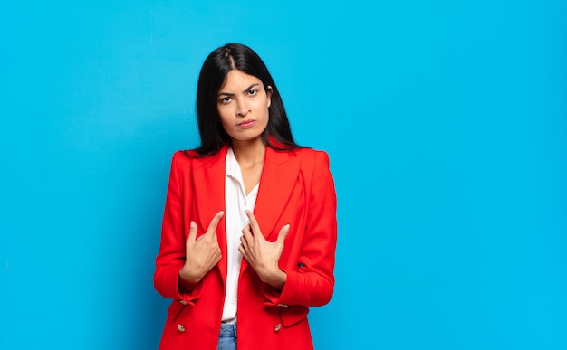 Młoda hiszpańska bizneswoman wskazująca na siebie z zakłopotanym i zagadkowym spojrzeniem, zszokowana i zaskoczona wyborem
