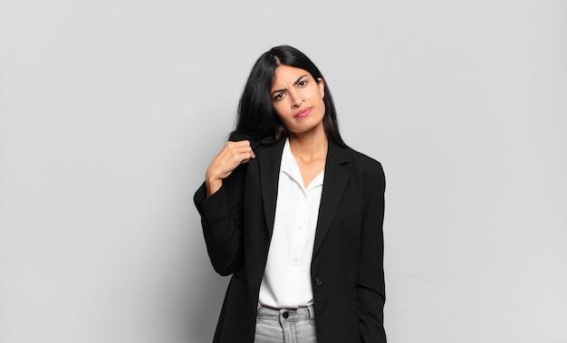 Młoda hiszpańska bizneswoman wygląda arogancko, odnosząc sukcesy, pozytywnie i dumnie, wskazując na siebie