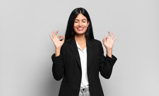 Młoda hiszpańska bizneswoman wygląda na skoncentrowaną i medytującą, czuje się usatysfakcjonowana i zrelaksowana, myśli lub dokonuje wyboru