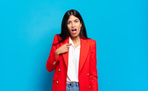 Młoda hiszpańska bizneswoman wygląda na zszokowaną i zaskoczoną z szeroko otwartymi ustami, wskazując na siebie