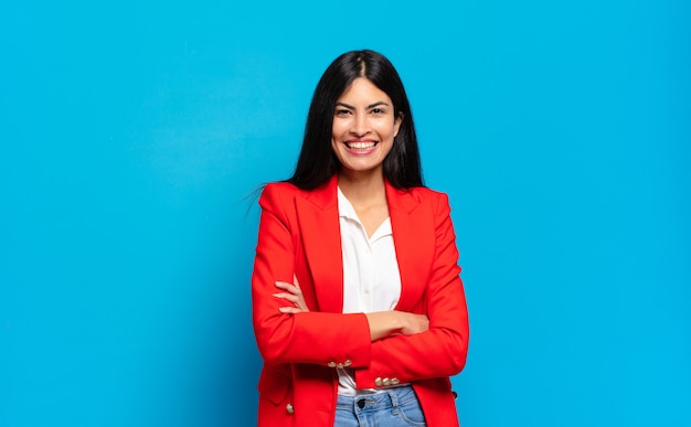 Młoda hiszpańska bizneswoman wyglądająca jak szczęśliwa, dumna i usatysfakcjonowana osoba, która uśmiecha się ze skrzyżowanymi rękami