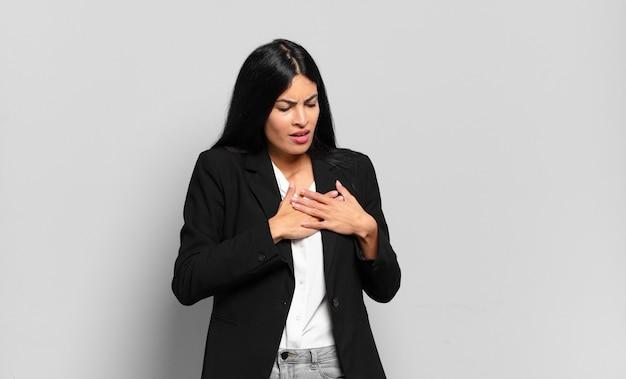 Młoda hiszpańska bizneswoman wyglądająca na smutną, zranioną i załamaną, trzymająca obie ręce blisko serca, płacząca i przygnębiona