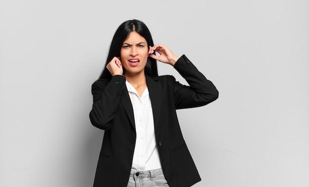 Młoda hiszpańska bizneswoman wyglądająca na wściekłą, zestresowaną i zirytowaną, zakrywającą obydwoje uszu ogłuszającym hałasem, dźwiękiem lub głośną muzyką