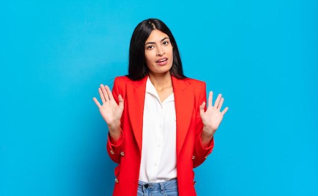 Młoda hiszpańska bizneswoman wyglądająca na zdenerwowaną, zaniepokojoną i zaniepokojoną, mówiącą, że to nie moja wina, albo nie zrobiłam tego
