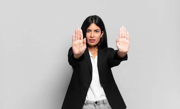 """Młoda hiszpańska bizneswoman wyglądająca poważnie, nieszczęśliwa, zła i niezadowolona, zabraniająca wejścia lub mówiąca """"stop"""" z obiema otwartymi dłońmi"""