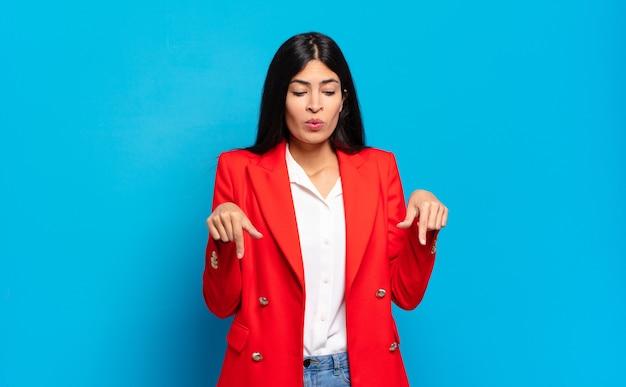 Młoda hiszpańska bizneswoman z otwartymi ustami skierowana w dół obiema rękami, wyglądająca na zszokowaną, zdumioną i zaskoczoną